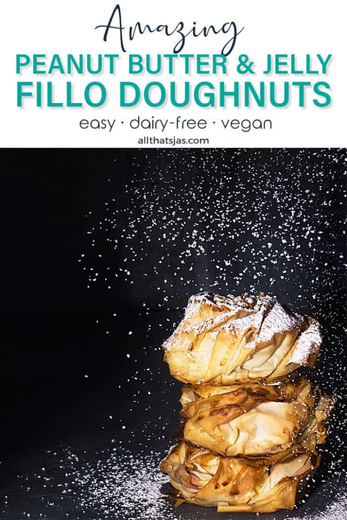 A front shot of three stacked donuts with a black background being dusted with sugar and with text overlay