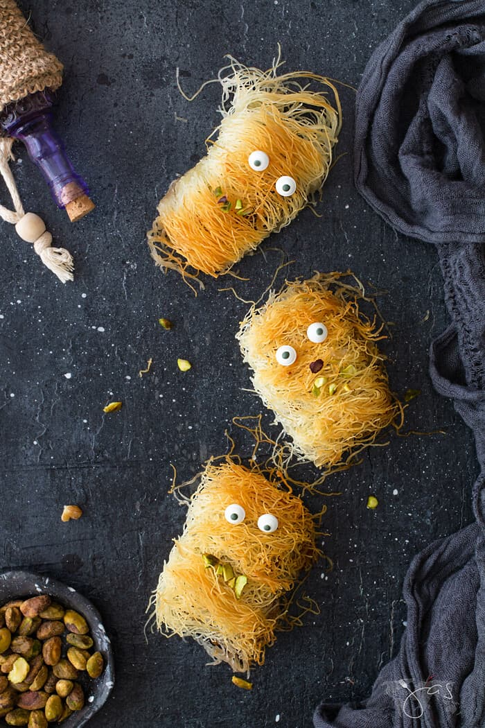 An overhead shot of three Fuzzy and mummy looking kataifi monsters on a black background