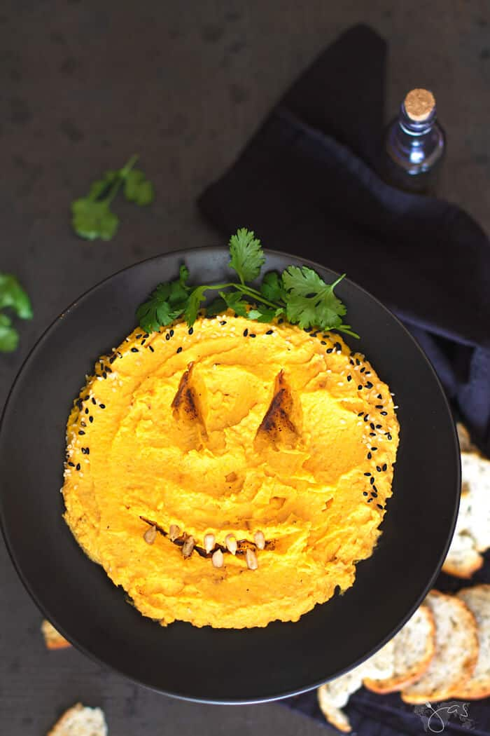 A flat Lay of Halloween Pumpkin Hummus Dip on a black towel and background.