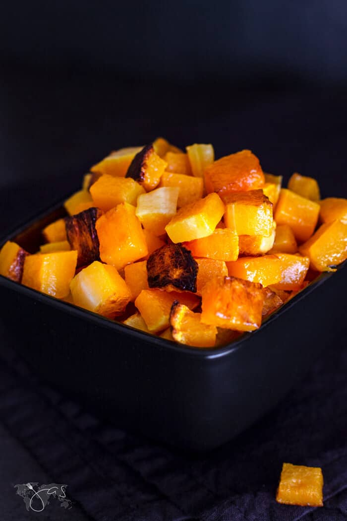Roasted pumpkin pieces in a black bowl with a black background