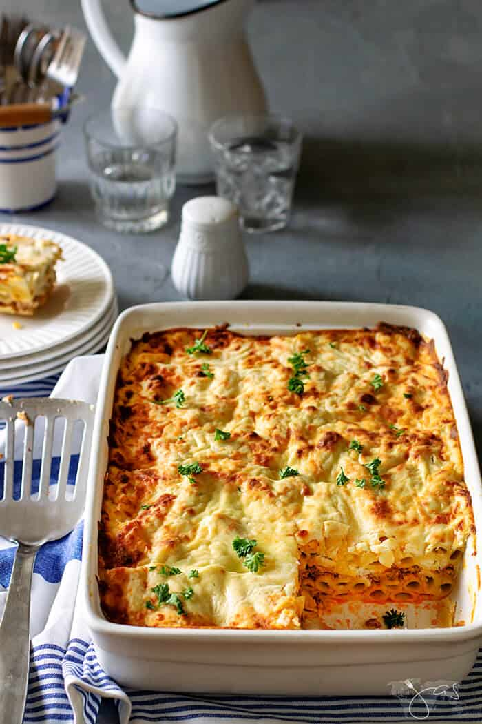 White casserole baking dish with Greek lasagna inside with one square serving removed