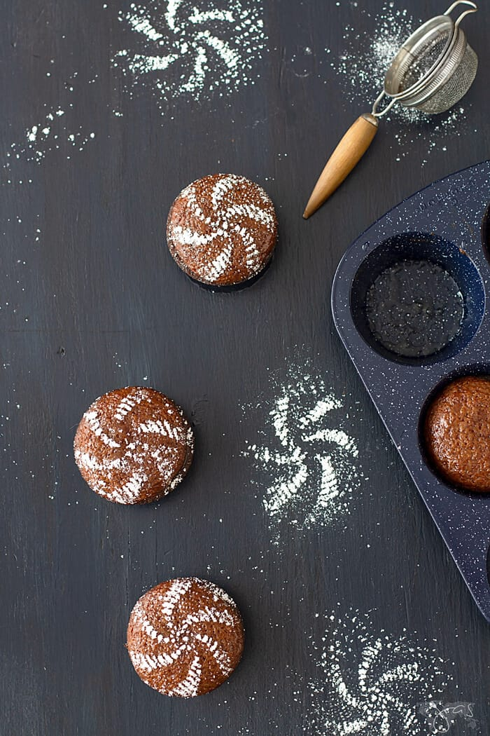 Three mini malva cakes on a dark background dusted with confectioners sugar.