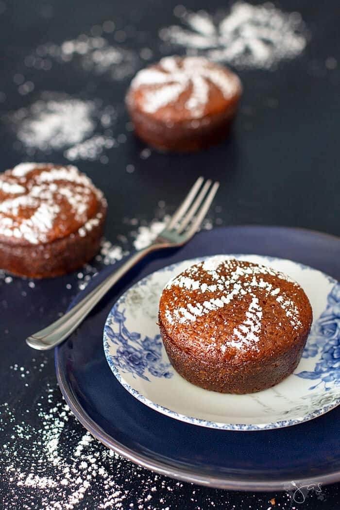 Three South African Malva Pudding Mini Cakes on a dark background dusted with powdered sugar in a cute pattern.