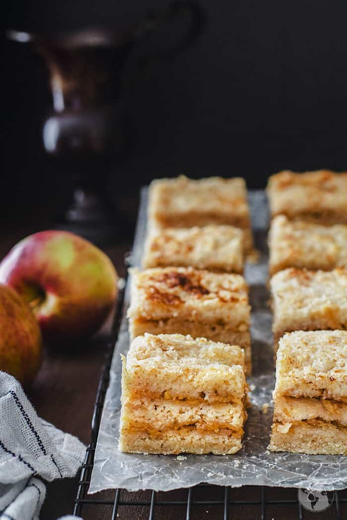 A close up shot of cake squares on a parchment paper with black background