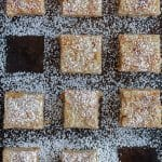 a flat lay of apple cake squares dusted with powdered sugar and two pieces removed