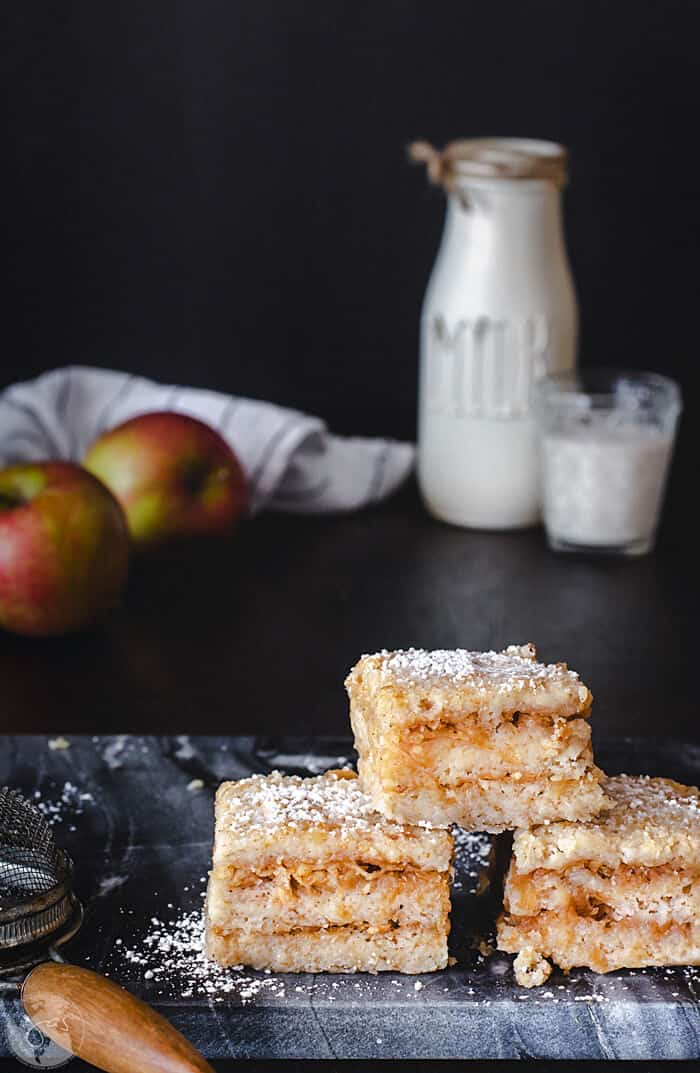 A front shot of three pieces of Croatian apple cake stacked on a with milk bottle and apples in the background