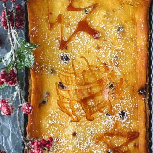 An overhead shot of cranberry tart with caramel garnishes and Christmas decorations.