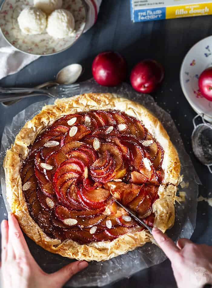 Slicing the rustic plum tart.
