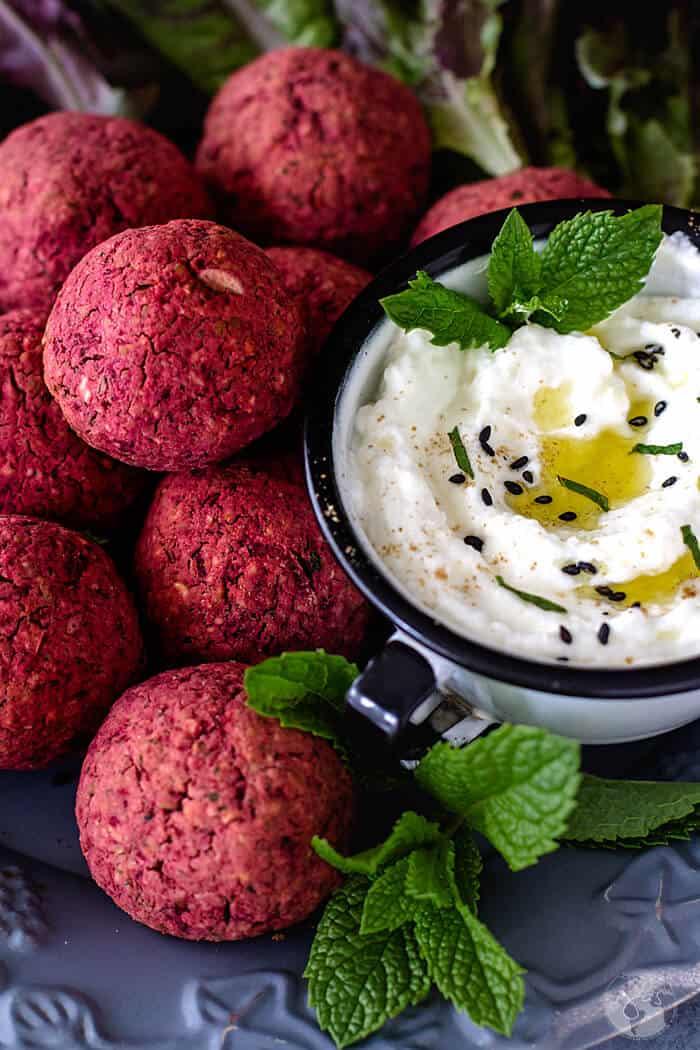 Close up of falafel and yogurt sauce.