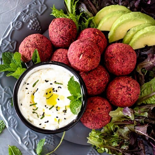 Falafel with red beetroot piled up on a plate with lettuce and yogurt sauce.