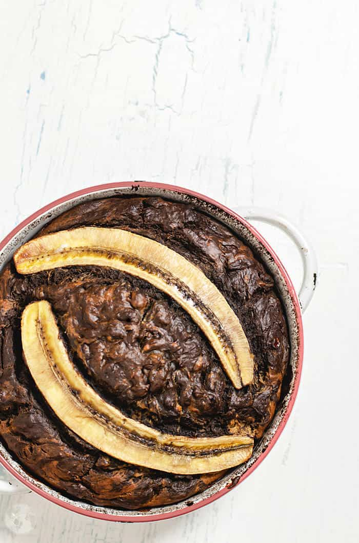 A round pan with chocolate banana bread topped with two banana halves on a white counter.