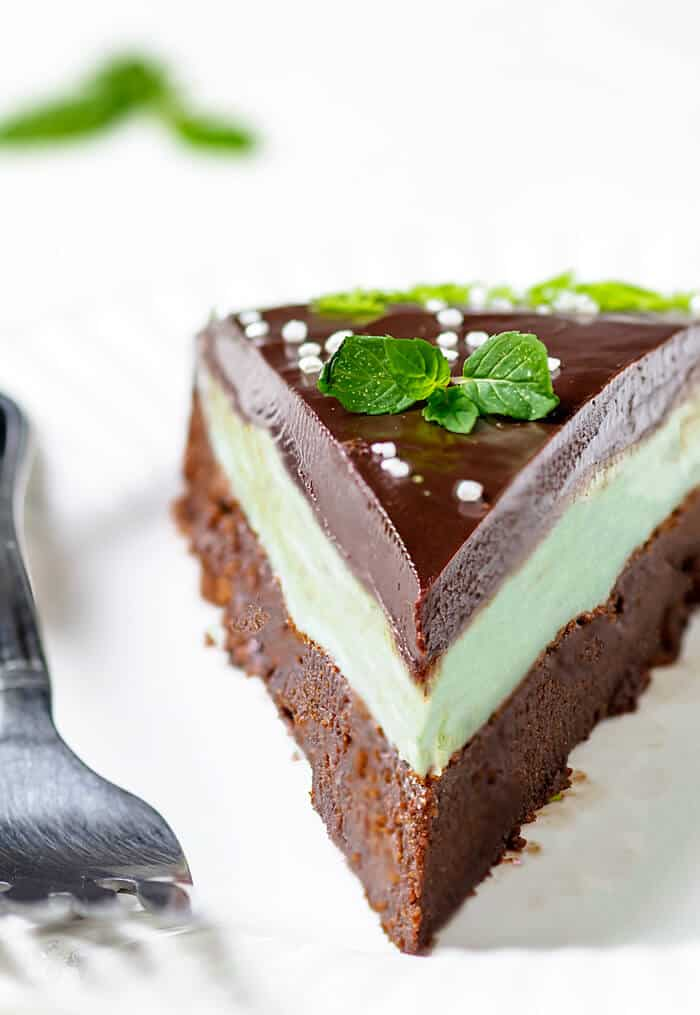 A close up of a mint chocolate cake slice with mint leaves and sprinkles.