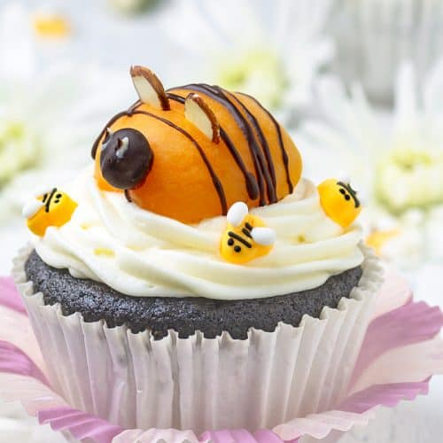 Adorable apricot bee sitting on top of cream cheese frosted chocolate cupcake.