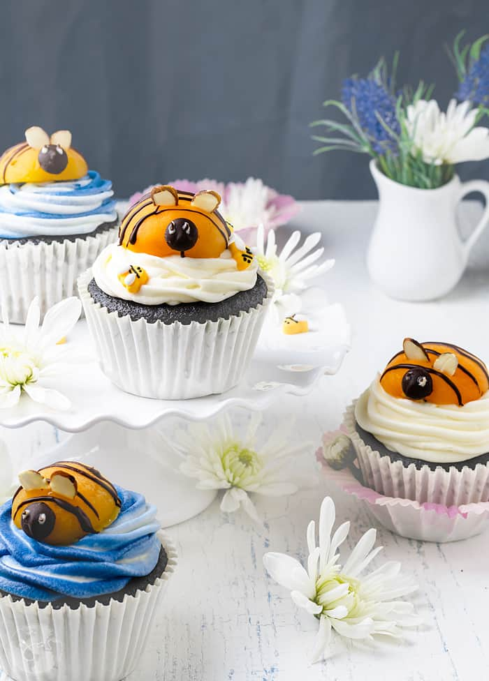 Blue and white cream cheese frosting and apricot bumblebees on chocolate cupcakes are perfect for spring.