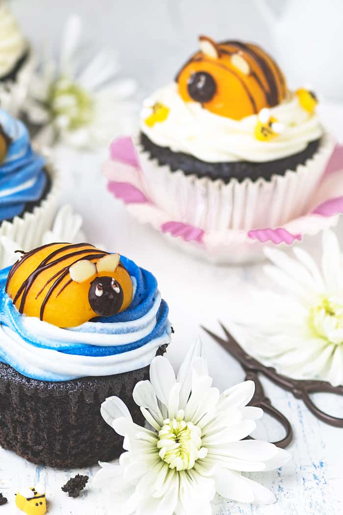 Two bumblebee cupcakes with flowers sitting on a table.