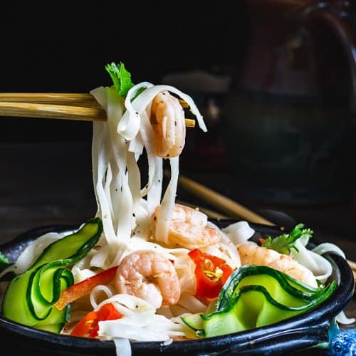 Rice noodles and shrimp on chopsticks over the Thai salad bowl.