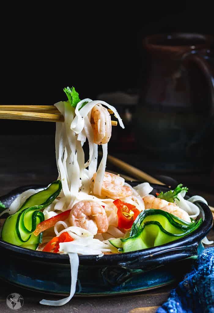 Rice noodles and shrimp on chopsticks over the Thai salad bowl.
