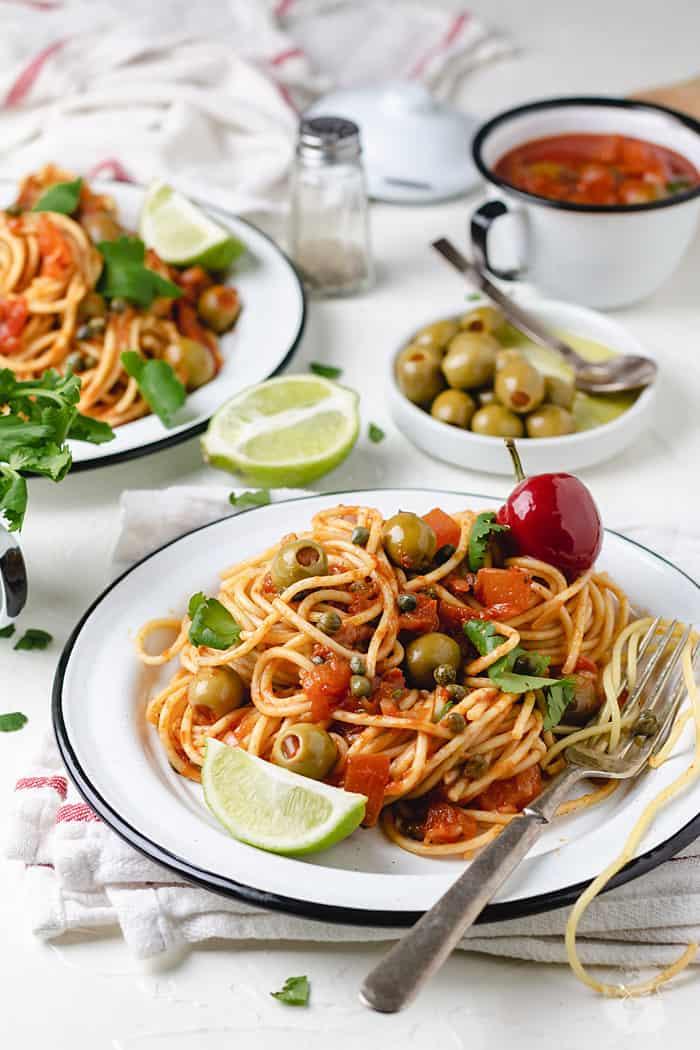Veracruz salsa, spaghetti, lime, and olives on a table.