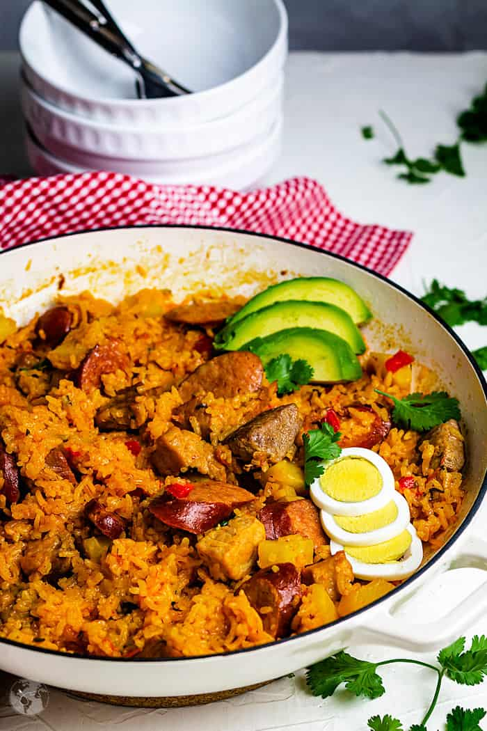 Traditional Colombian delicacy - pork and sausage risotto with boiled eggs and avocado