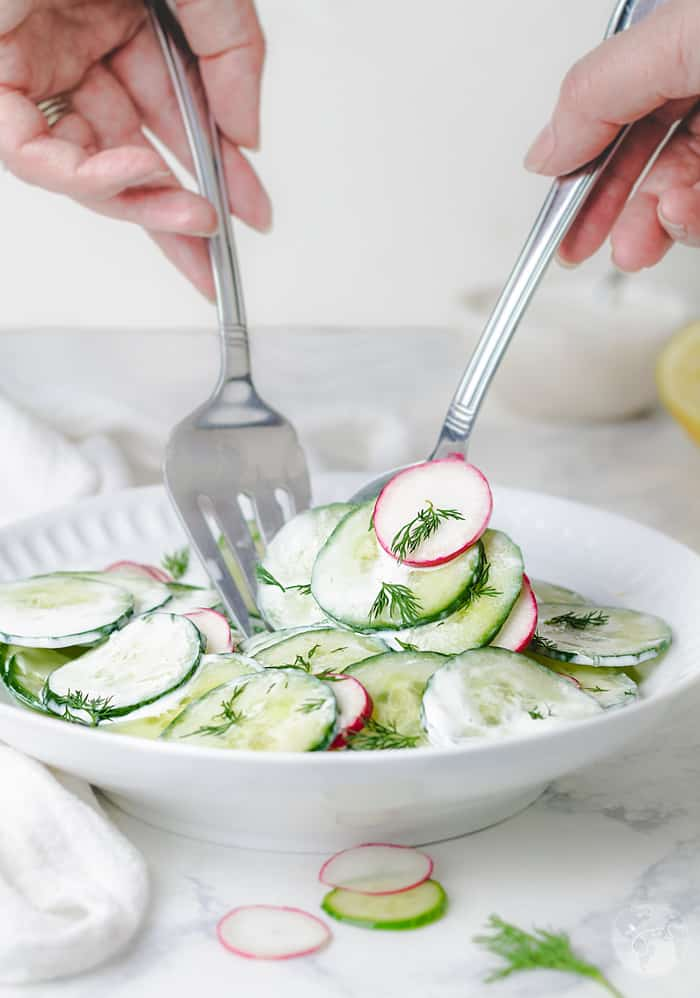 Tossing the cucumber salad with sour cream and dill.