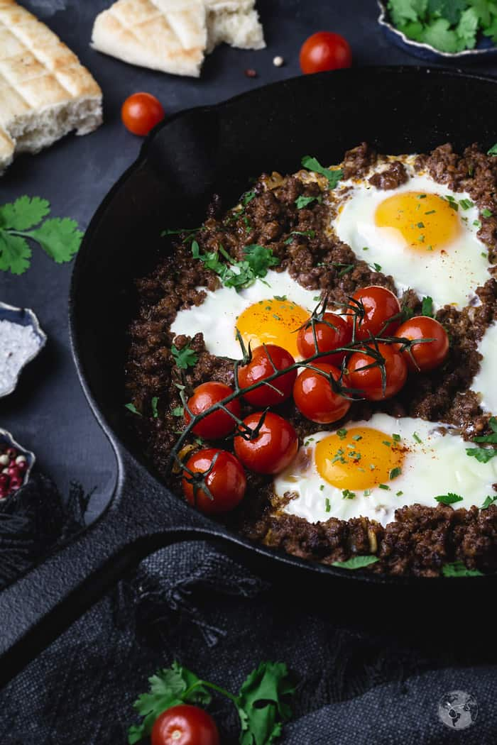 Poached eggs over minced lamb in a skillet with cherry tomatoes