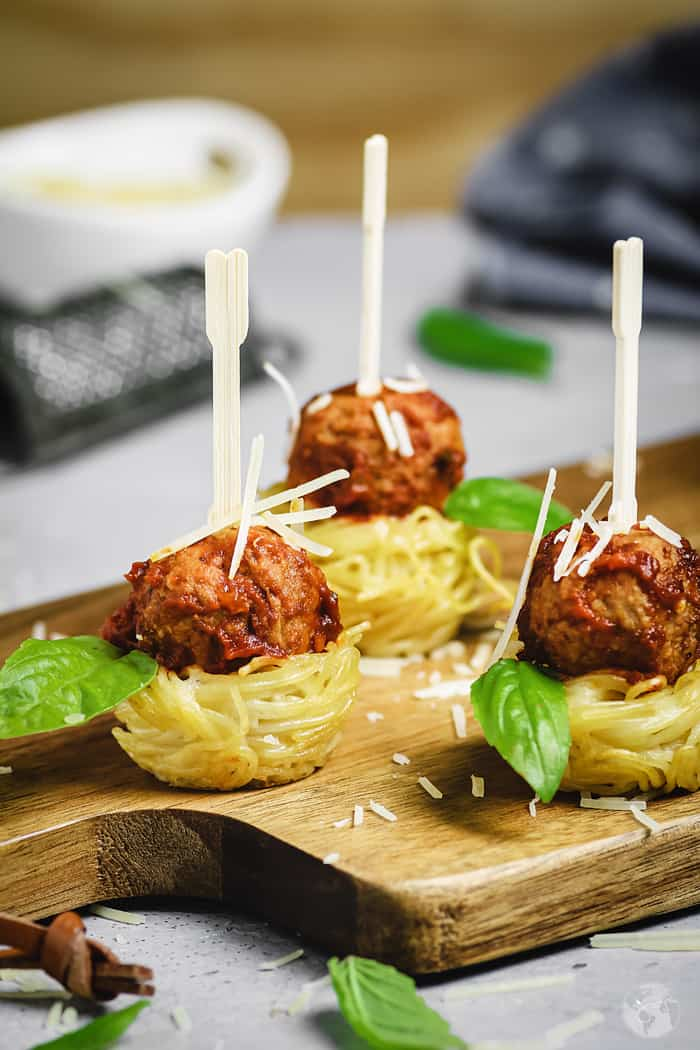 Spaghetti nests appetizer with meatballs with toothpicks.