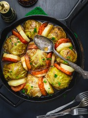 An overhead shot of Palestinian Stuffed Savoy Cabbage Rolls in a cast Iron skillet on a black background