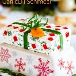Festive garlic dill cream cheese schmear wrapped like a Christmas gift