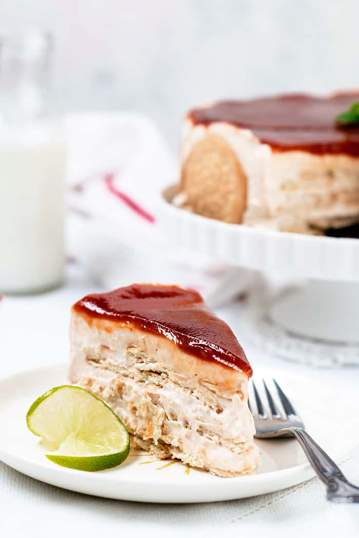 A large slice of Charlotte cake topped with guava sauce.