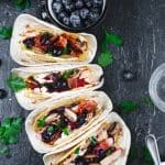 Four tacos lineup with turkey meat and a bowl with blueberries.