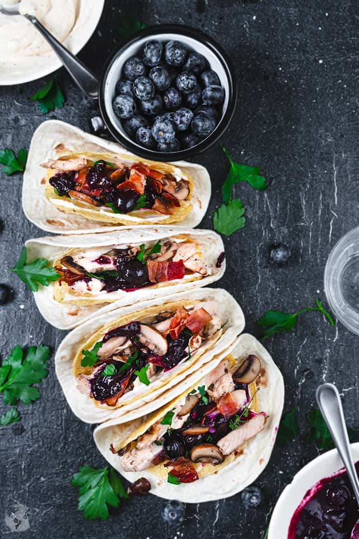 Four tacos lineup with turkey meat, mushrooms, bacon, and blueberry sauce.