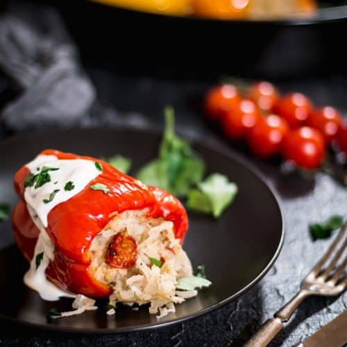 Pepper stuffed with potato and rice mixture with roasting pan and tomatoes on the vine in the background.