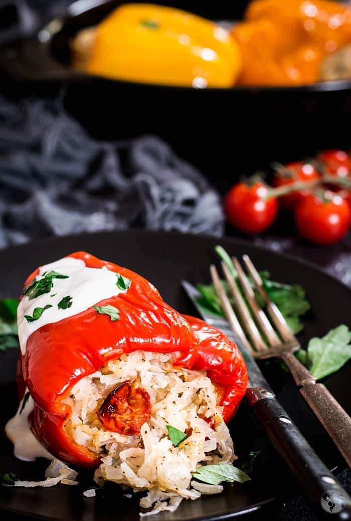 Red bell pepper stuffed with potato and rice mixture on a black plate.