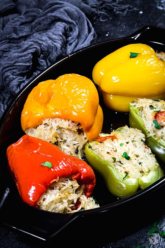 Whole and halved peppers stuffed with grated potato mixture.