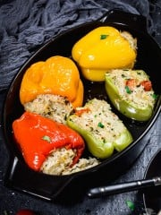 Stuffed peppers in a black baking dish.