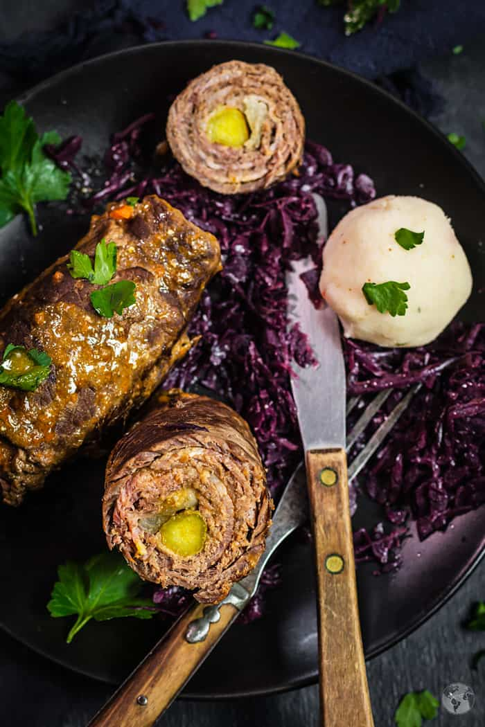 A close up shot of rouladen on a plate with rotkohl and a fork and knife