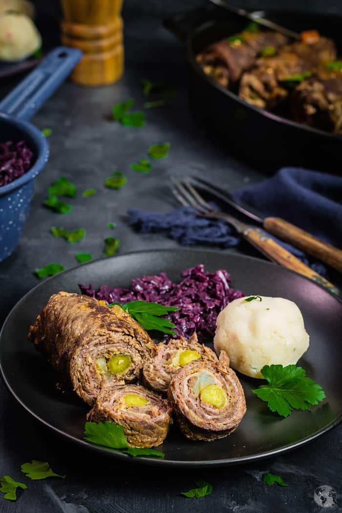 black plate on a dark blue background with rouladen, red cabbage, and dumplings.