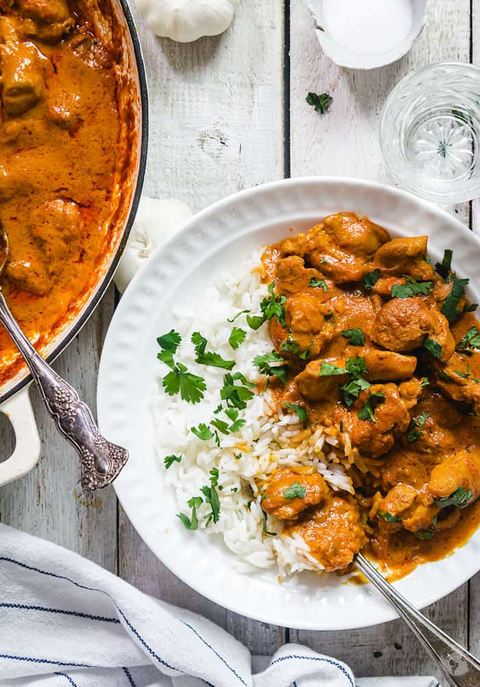 Orange-colored chicken tikka masala with rice in a white plate with white wooden background