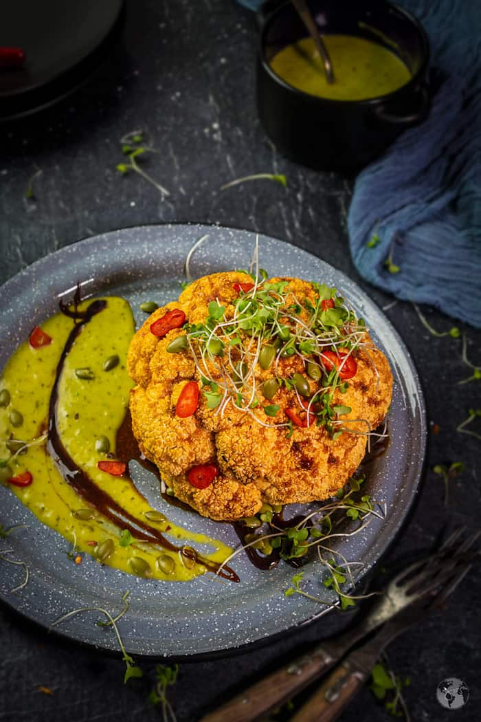 Easy to make oven-baked whole head of cauliflower, spiced with chili pepper and topped with pepitas and microgreens.