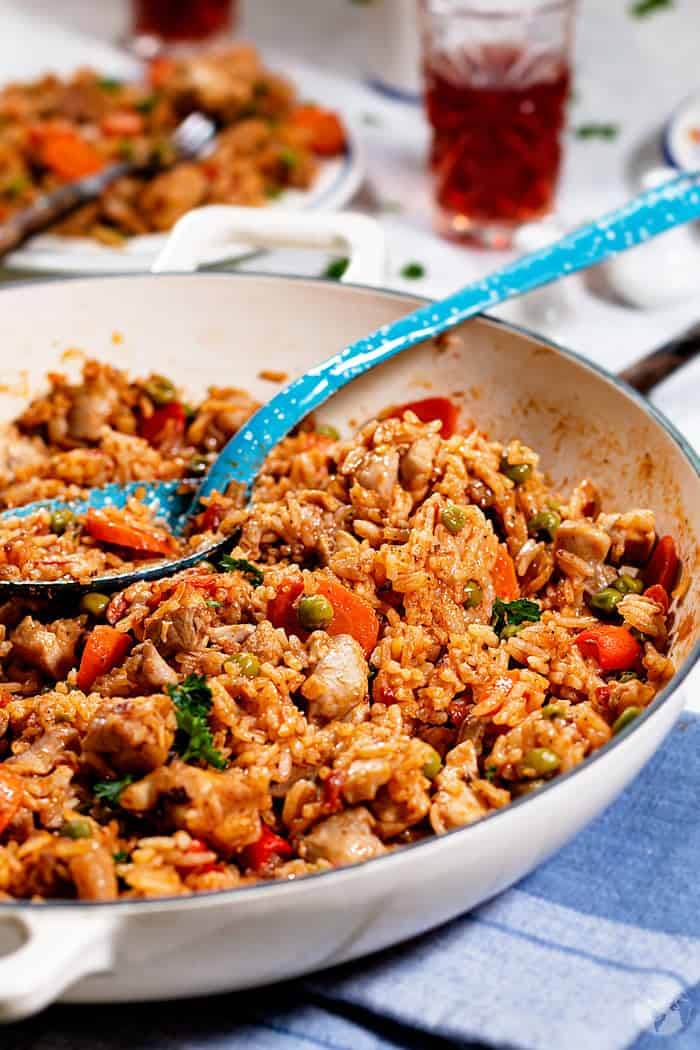 Rice with vegetables and pieces of chicken thighs in a white enamel cast-iron skillet