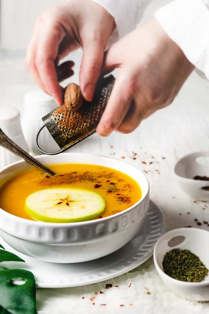 Grating a whole nutmeg over a bowl of squash soup