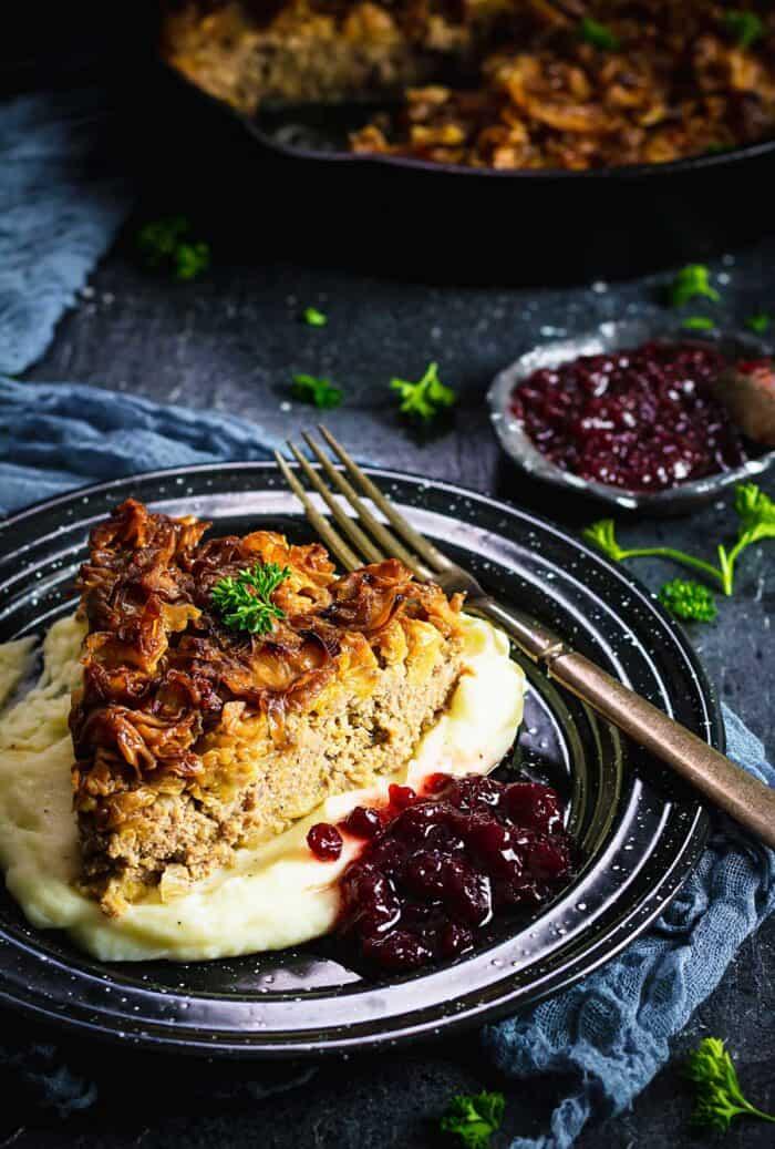 A slice of cabbage pudding over mashed potatoes.