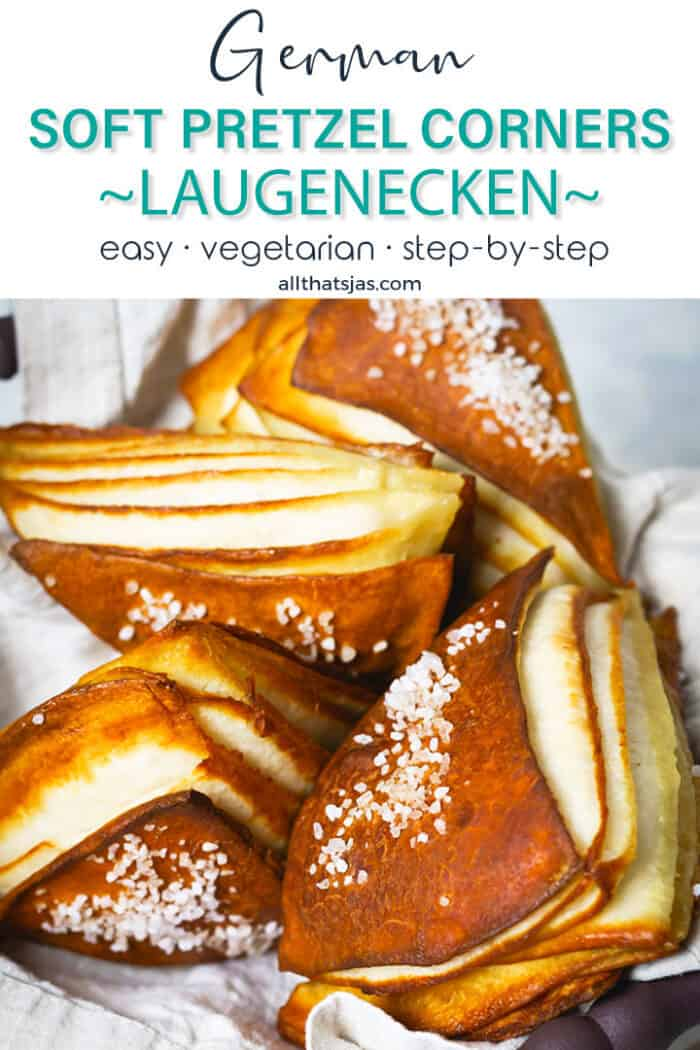 Laugenecken stacked on top of each other in a basket, sprinkled with coarse salt. Text overlay.