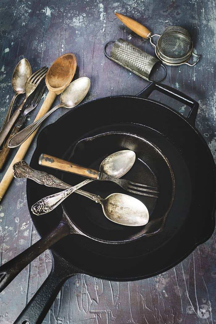 Clean and seasoned iron skillets with kitchen utensils.