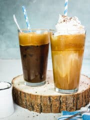 Two glasses with Greek frappe on a round slab of wood and light blue background.