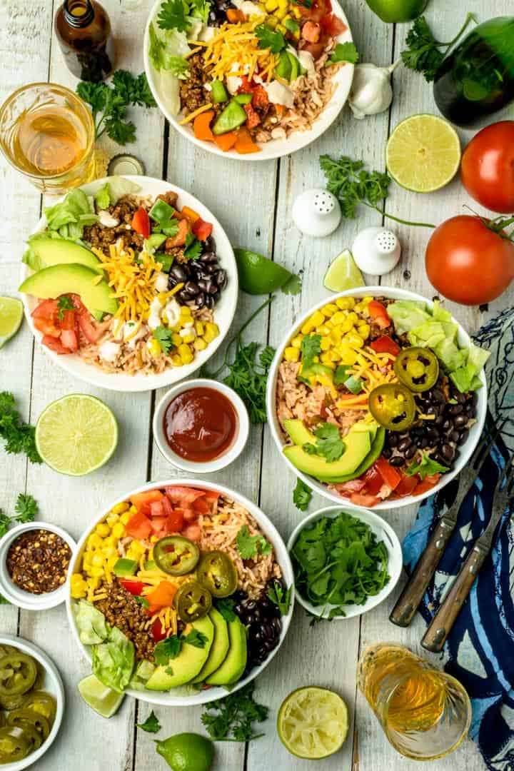 An overhead shot of 4 burrito bowls surrounded with smaller bowls with ingredients and condiments