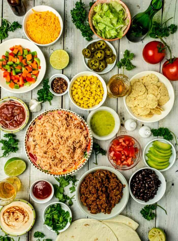 All ingredients and toppings for chipotle burrito bowl recipe placed in separate bowls