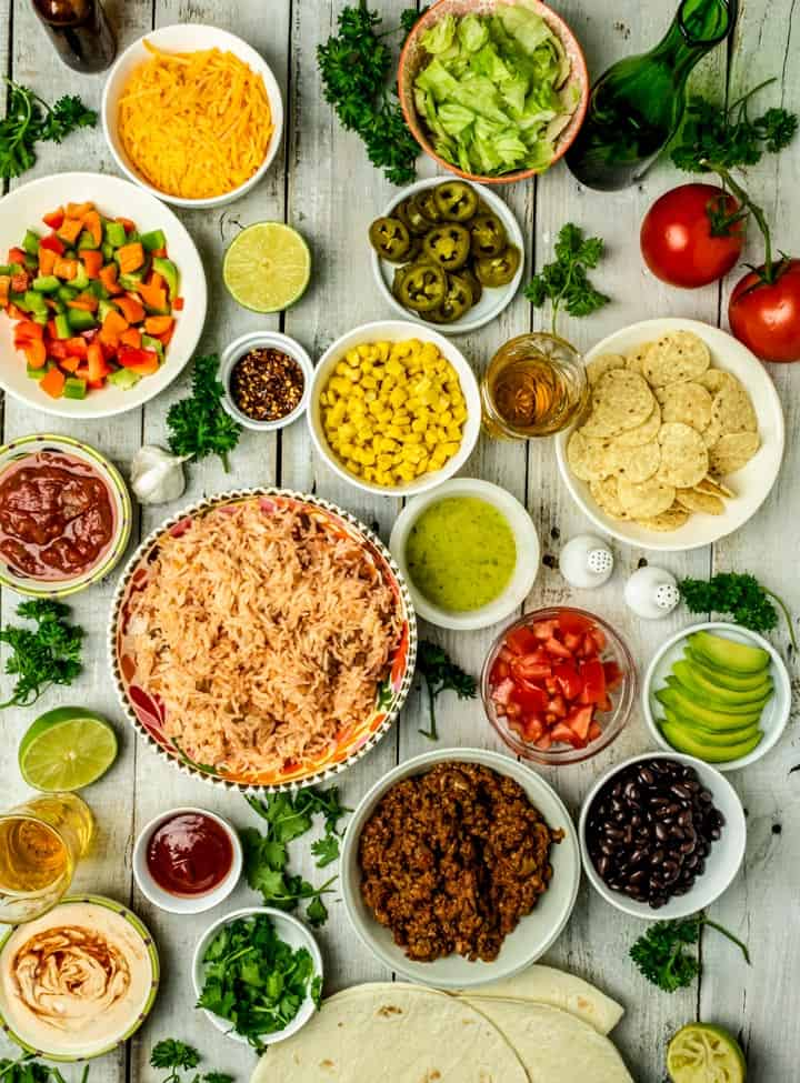 An overhead shot of all ingredients and toppings for chipotle burrito bowl recipe placed in separate bowls