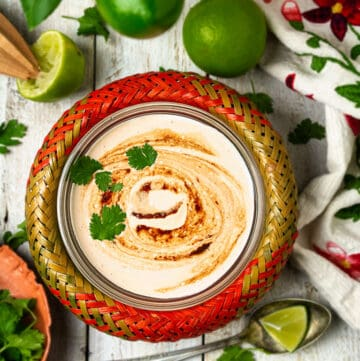 Mexican spicy burrito dressing with limes and cilantro on a white wooden background.