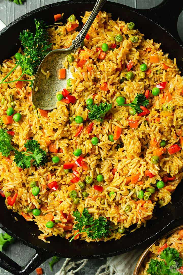 A close up of the djuvec side with rice, peas, peppers, and carrots, sprinkled with parsley.